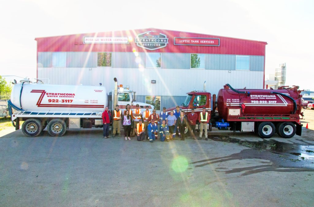 Photo of employees and trucks
